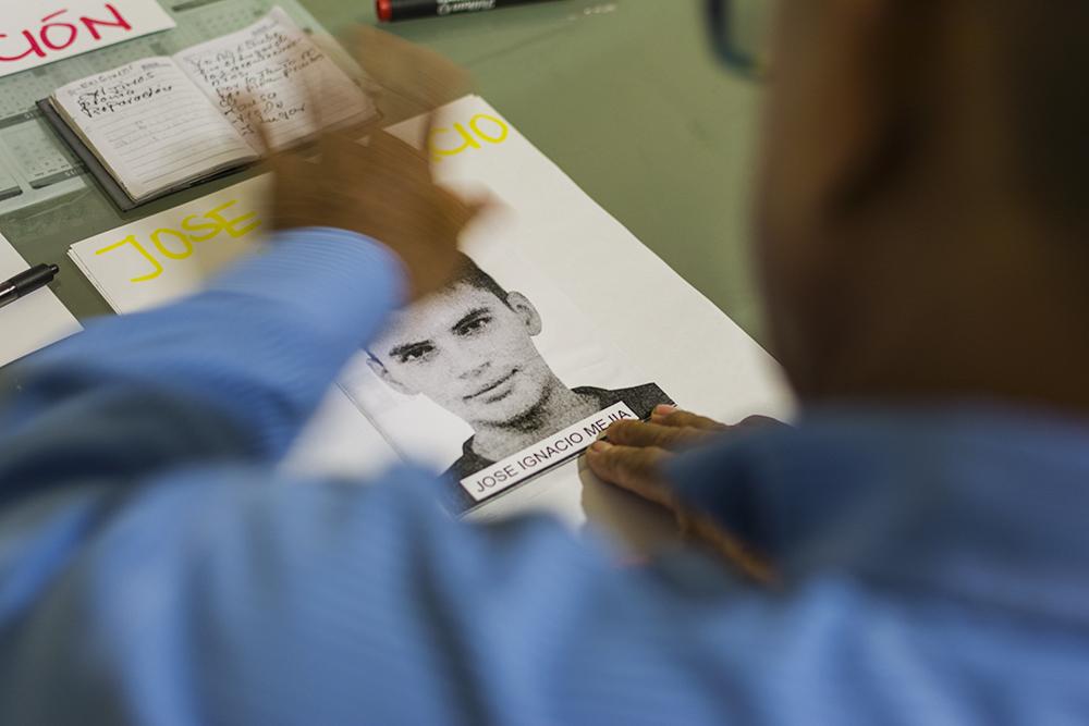 Familiar prepara un cartel que llevará a la entrega del los restos de su hijo